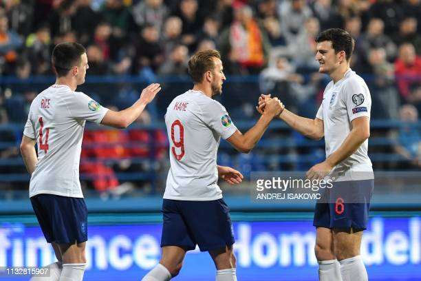 England's forward Harry Kane is congrulated by England's defender Harry Maguire and England's defender Declan Rice after scoring the fourth goal of...