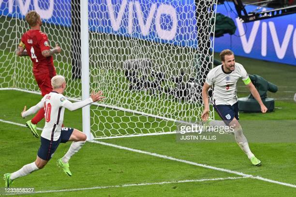 England's forward Harry Kane runs in celebration after scoring the second goal during the UEFA EURO 2020 semi-final football match between England...