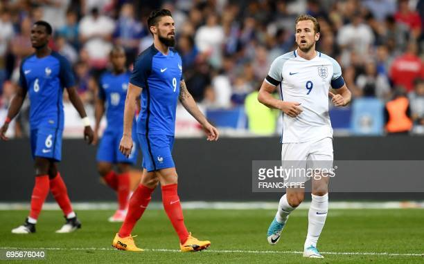 England's forward Harry Kane runs past France's forward Olivier Giroud after scoring a penalty during the international friendly football match...
