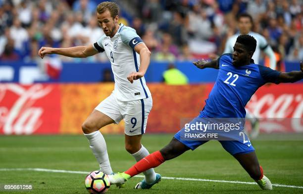 England's forward Harry Kane runs with the ball past France's defender Samuel Umtiti during the international friendly football match between France...