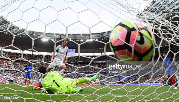 England's forward Harry Kane scores a penalty past France's goalkeeper Hugo Lloris during the international friendly football match between France...