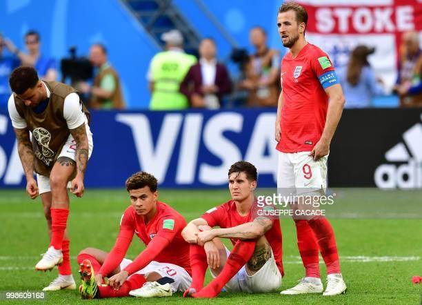 TOPSHOT England's forward Harry Kane stands past England's defender Harry Maguire England's midfielder Dele Alli and England's defender Kyle Walker...
