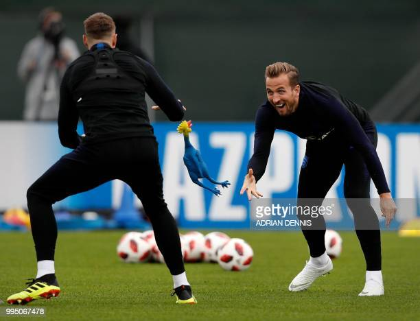 England's forward Harry Kane throws a toy rooster to defender Phil Jones as they take part in a training session in Repino on July 10 2018 ahead of...