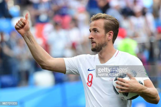 England's forward Harry Kane who scored a hattrick holds the match ball at the end of the Russia 2018 World Cup Group G football match between...