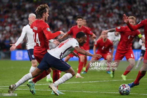 England's forward Raheem Sterling falls on the ground which led to the awarding of a penalty during the UEFA EURO 2020 semi-final football match...