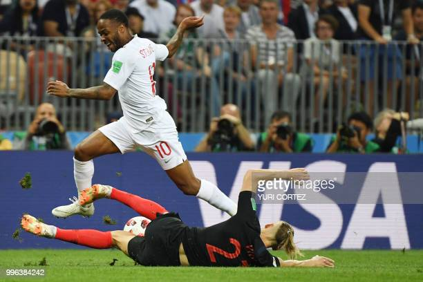 England's forward Raheem Sterling jumps over Croatia's defender Domagoj Vida during the Russia 2018 World Cup semi-final football match between...