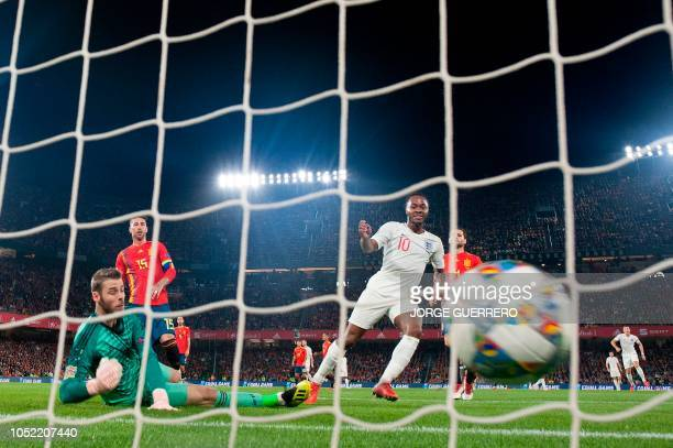 England's forward Raheem Sterling scores against Spain's goalkeeper David de Gea during the UEFA Nations League football match between Spain and...