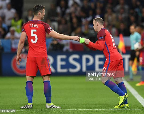 England's forward Wayne Rooney receives the captain's armband from England's defender Gary Cahill after coming on during the Euro 2016 group B...