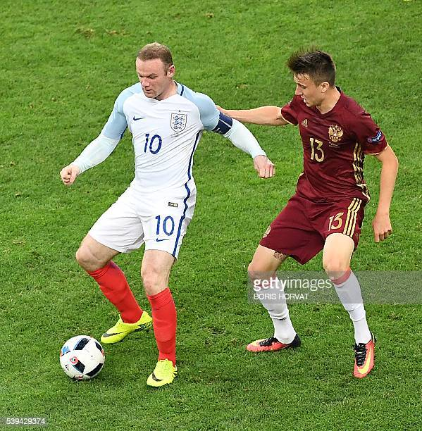 England's forward Wayne Rooney vies with Russia's midfielder Aleksandr Golovin during the Euro 2016 group B football match between England and Russia...