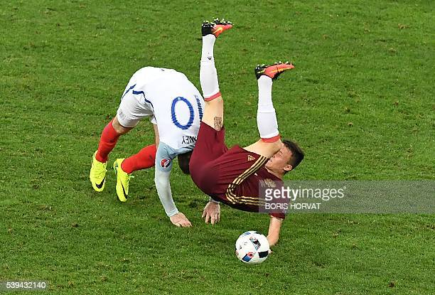 TOPSHOT England's forward Wayne Rooney vies with Russia's midfielder Aleksandr Golovin during the Euro 2016 group B football match between England...