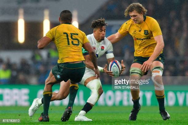 England's fullback Anthony Watson runs between Australia's fullback Kurtley Beale and Australia's flanker Ned Hanigan during the international rugby...