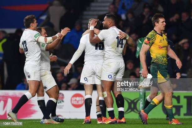 England's fullback Elliot Daly celebrates with teammates after scoring a try during the international rugby union test match between England and...