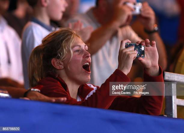 England's Gemma Gibbons takes photos of her husband Scotland's Euan Burton receiving his gold medal for defeating Pakistan's Shah Hussain Shah in...