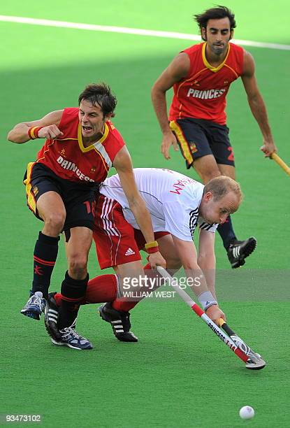 England's Glenn Kirkham is tackled by Spain's Rodrigo Garza and Eduard Arbos during their Champions Trophy field hockey match in Melbourne on...