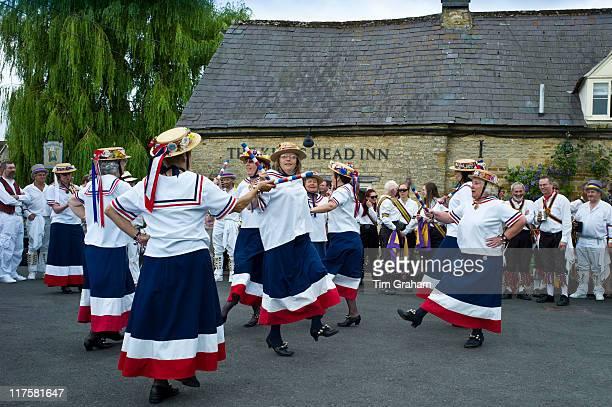 England's Glory Ladies Morris dancers perform a dancing display at The Kings Head Pub in Bledington Oxfordshire UK