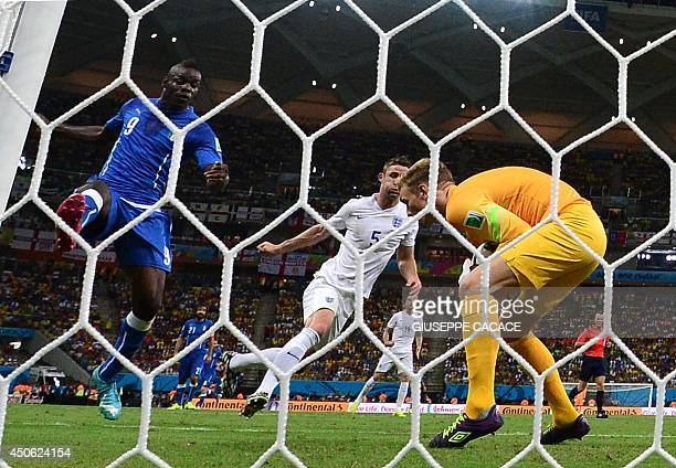 England's goalkeeper Joe Hart saves an attempt by Italy's forward Mario Balotelli during a Group D football match between England and Italy at the...