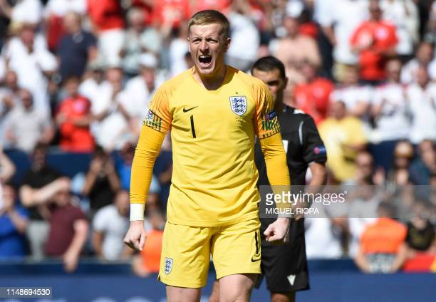 England's goalkeeper Jordan Pickford celebrates a goal during the penalty shootout during the UEFA Nations League third place football match between...