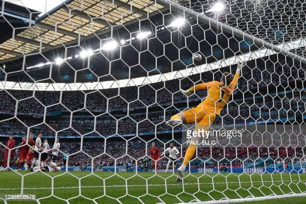 England's goalkeeper Jordan Pickford concedes a goal during the UEFA EURO 2020 semi-final football match between England and Denmark at Wembley...