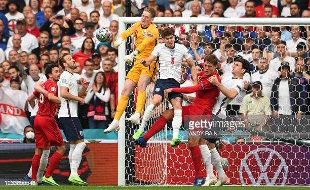 England's goalkeeper Jordan Pickford deflects a corner kick during the UEFA EURO 2020 semi-final football match between England and Denmark at...