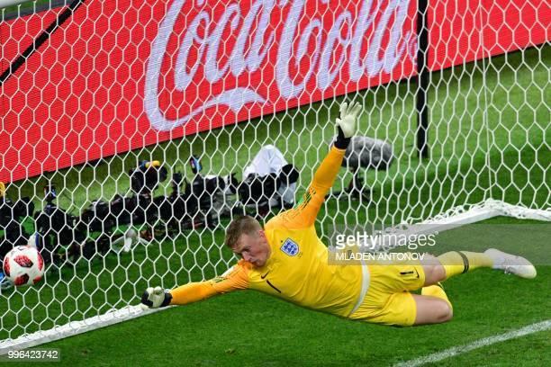 England's goalkeeper Jordan Pickford dives and take Croatia's first goal during the Russia 2018 World Cup semi-final football match between Croatia...