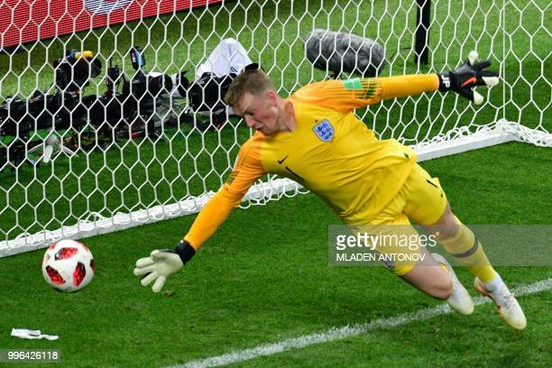 England's goalkeeper Jordan Pickford dives and take Croatia's first goal during the Russia 2018 World Cup semifinal football match between Croatia...