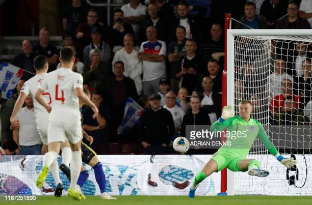 England's goalkeeper Jordan Pickford dives but fails to save a shot from Kosovo's midfielder Valon Berisha during the UEFA Euro 2020 qualifying Group...