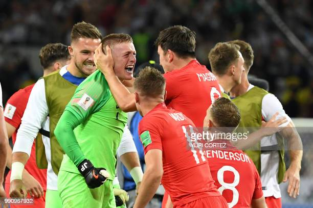 TOPSHOT England's goalkeeper Jordan Pickford England's defender Harry Maguire and teammates celebrate after winning the penalty shootout at the end...