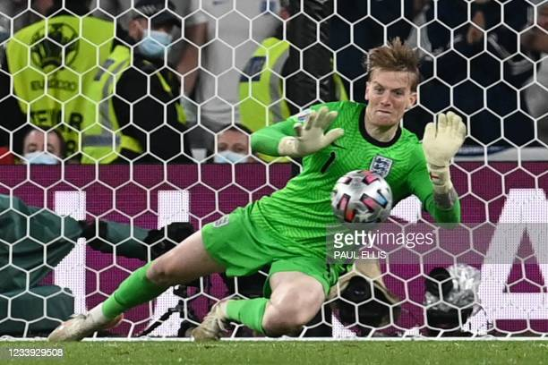 England's goalkeeper Jordan Pickford saves a shot by Italy's forward Andrea Belotti in the penalty shootout during the UEFA EURO 2020 final football...
