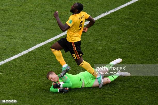 TOPSHOT England's goalkeeper Jordan Pickford saves the ball ahead of Belgium's forward Romelu Lukaku during their Russia 2018 World Cup playoff for...