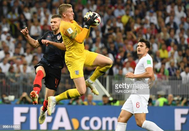 TOPSHOT England's goalkeeper Jordan Pickford stops a shot on goal by Croatia's forward Ante Rebic next to England's defender Harry Maguire during the...
