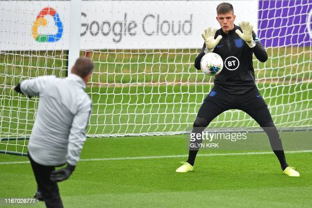 England's goalkeeper Nick Pope makes a save during an England team training session at Staplewood Campus in southampton southern England on September...