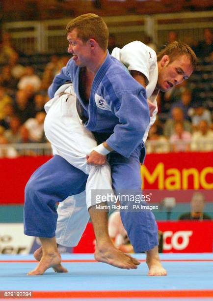 England's Gold medal winner James Warren tangles with Scotland's David Somerville in the final of the under Men's 66 kg Judo class during the...