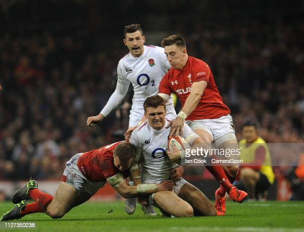 Englands Henry Slade is tackled by Wales' Hadleigh Parkes and Josh Adams during the Guinness Six Nations match between Wales and England at...