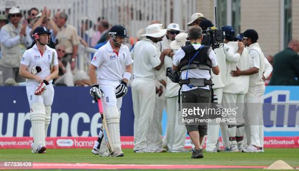 England's Ian Bell and Eoin Morgan return to the field of play after tea as the Indian team form a huddle.