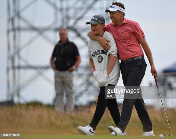 England's Ian Poulter and his son Luke walk the 4th hole during a practice round at The 147th Open golf Championship at Carnoustie Scotland on July...