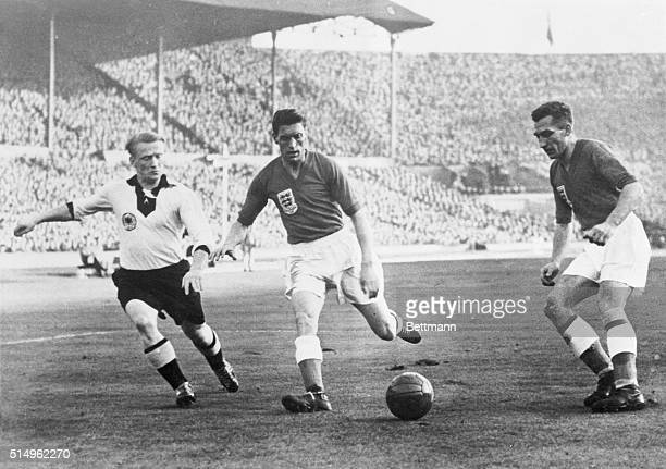 England's inside right Roy Bentley boots the ball goalward as an unidentified German player attempts to thwart his maneuver in a game between the...