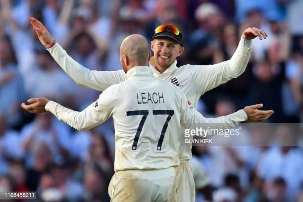 England's Jack Leach celebrates with England's captain Joe Root after taking the wicket of Australia's Nathan Lyon during play on the fourth day of...