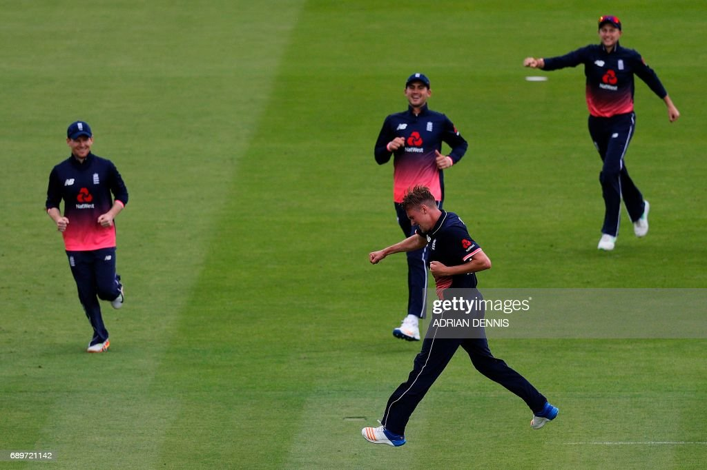 England's Jake Ball (bottom) celebrates with team mates after taking the wicket of South Africa's Faf du Plessis (unseen) for 5 runs to a catch by England's Jos Buttler (unseen) during the third One-Day International (ODI) cricket match between England and South Africa at Lord's Cricket Ground in London on May 29, 2017. / AFP PHOTO / Adrian DENNIS