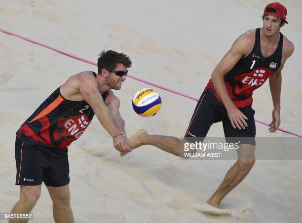 England's Jake Sheaf returns a ball watched by teammate Chris Gregory against New Zealand in the bronze medal match of the men's beach volleyball at...