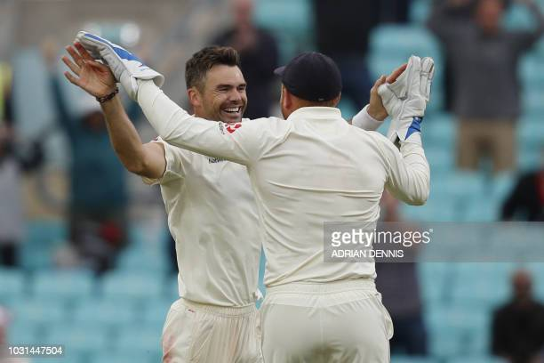 England's James Anderson celebrates with England's Jonny Bairstow after taking the wicket of India's Mohammed Shami on the final day of the fifth...