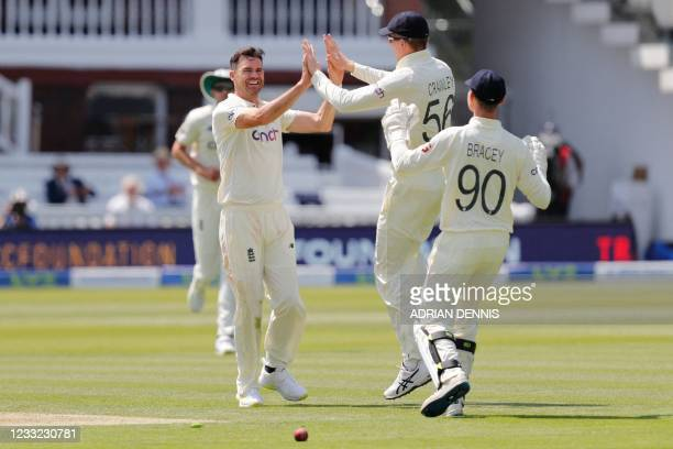 England's James Anderson celebrates with England's Zak Crawley and England's James Bracey after taking the wicket of New Zealand's captain Kane...