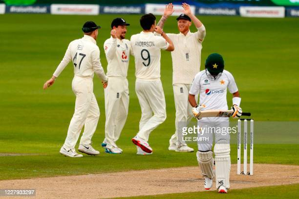 England's James Anderson celebrates with teammates after taking the wicket of Pakistan's Babar Azam for 69 in the opening over on the second day of...