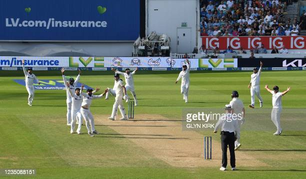England's James Anderson reacts after losing his wicket during play on the fifth day of the fourth cricket Test match between England and India at...