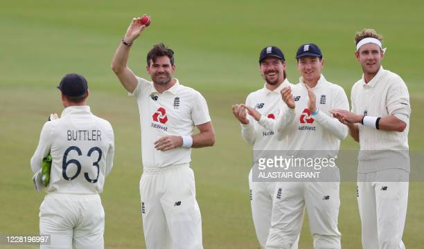 England's James Anderson shows the ball as he is applauded by teammates after taking the wicket of Pakistan's Azhar Ali, his 600th test match wicket,...