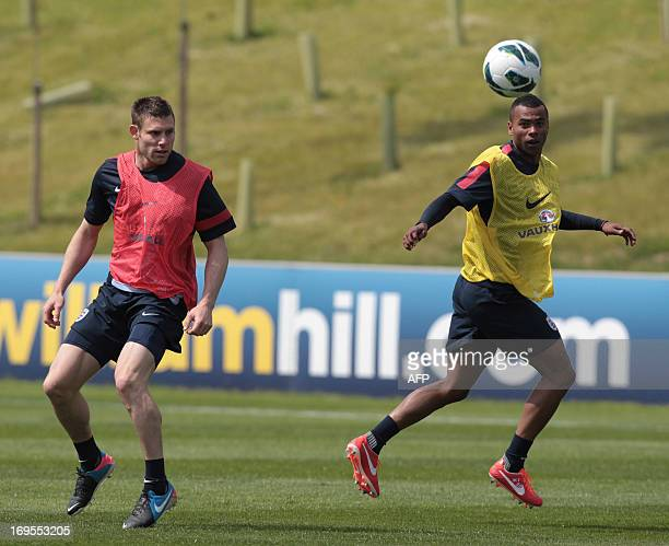 England's James Milner and Ashley Cole vie for the ball during a team training session at the Saint George's Park National Football Centre in...