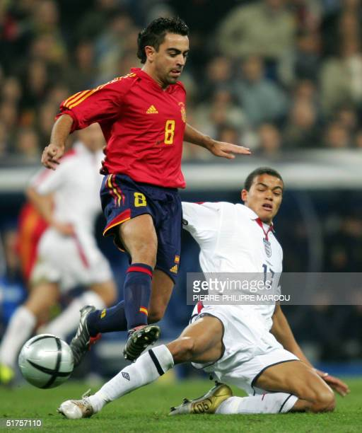 England's Jermaine Jenas tackles Spain's Xavi during their friendly football match in Santiago Bernabeu Stadium in Madrid 17 November 2004 AFP...