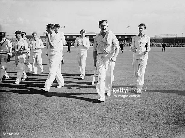 England's Jim Laker walks off the field at Old Trafford after taking all ten Australian wickets for just 53 runs in the second innings to win England...