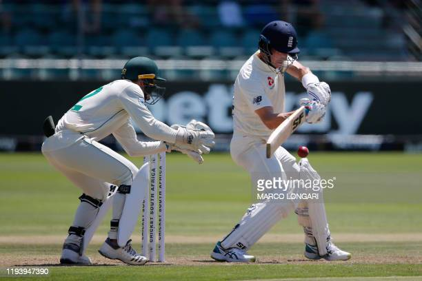England's Joe Denly plays a shot as South Africa's Quinton de Kock looks on during the first day of the third Test cricket match between South Africa...