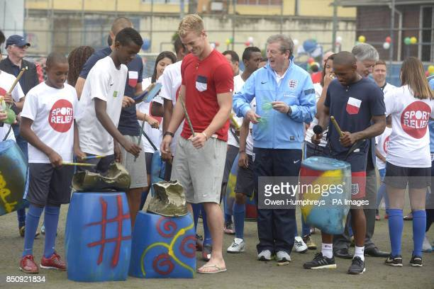 England's Joe Hart Roy Hodgson and Jermain Defoe play some instruments as they meet children from a Sport Relief funded project in Bola Pra Frente...