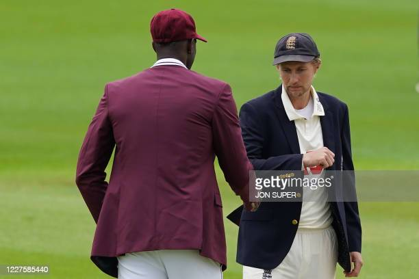 England's Joe Root and West Indies' Jason Holder bump elbows after the toss on the first day of the second Test cricket match between England and the...